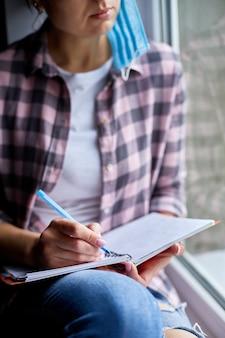 Donna seduta alla finestra, che scrive su un quaderno, per fare la lista dopo la fine della quarantena, fine del coronovirus