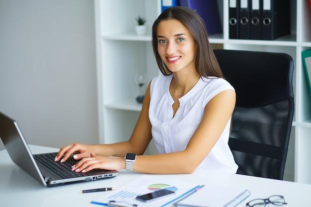 Donna seduta alla scrivania, lavorando sul portatile in ufficio moderno