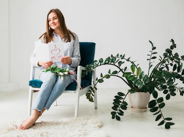 Donna seduta con biglietto di auguri e fiori