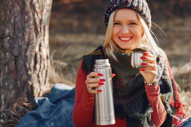 Donna seduta da un albero in una foresta di primavera con un drink thermos