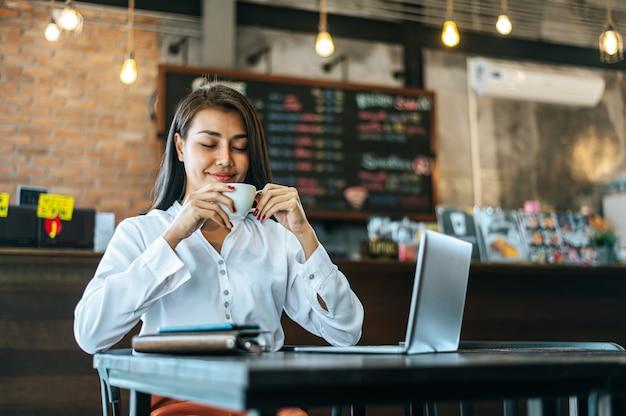 Donna seduta felicemente a bere il caffè nel negozio di caffè e laptop