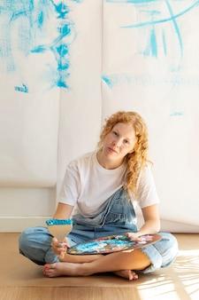 Donna seduta full shot con oggetti di pittura