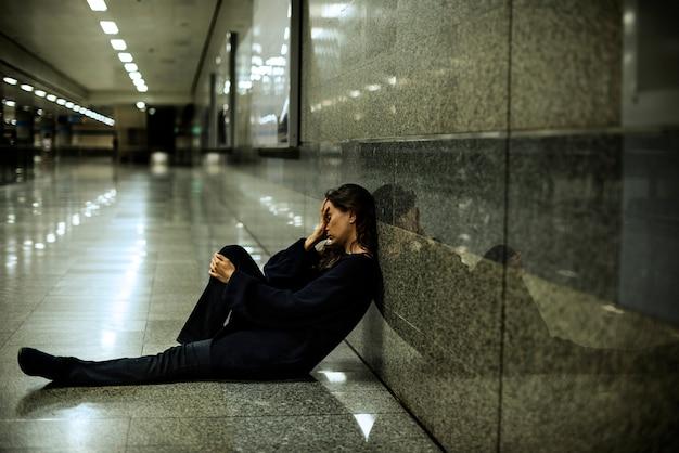Donna seduta senza speranza sul pavimento