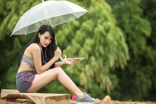 Donna seduta solitaria con ombrello. concetto di prendersi una pausa