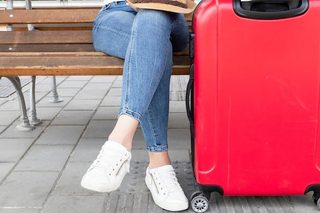 Donna seduta su una panchina con i bagagli