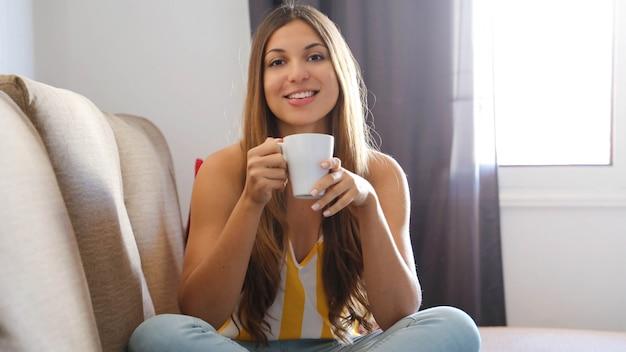 Donna seduta sul divano con le gambe incrociate in possesso di una tazza di caffè