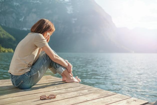 Donna seduta sul lago