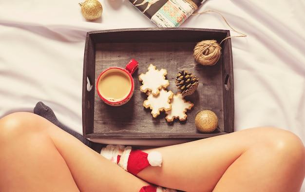 Donna seduta sul letto con decorazioni natalizie, accogliente appartamento disteso, vacanza pigra. opaco colorato