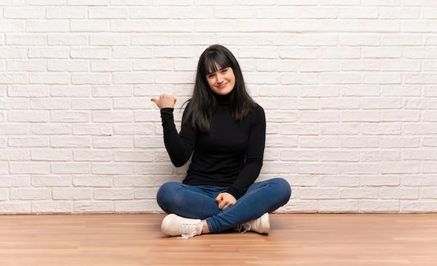 Donna seduta sul pavimento che punta verso il lato per presentare un prodotto