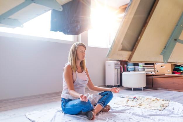 Donna seduta sul pavimento e l'esecuzione di yoga nel suo studio d'arte.