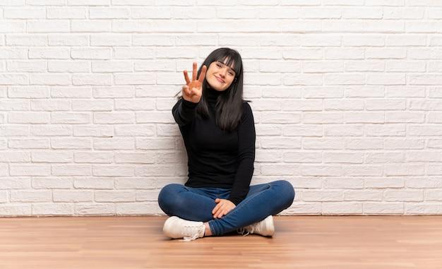 Donna seduta sul pavimento felice e contando tre con le dita
