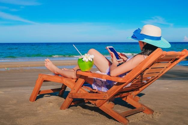 Donna seduta sulla sedia vicino al mare blu e bere succo di cocco sulla spiaggia in ho