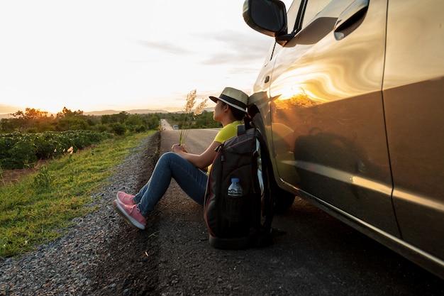 Donna seduta sulla strada al tramonto con auto e zaini concetto di vacanza e viaggi