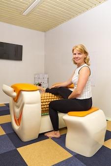 Donna seduta sullo strumento di massaggio per le gambe con una grande gioia sul viso