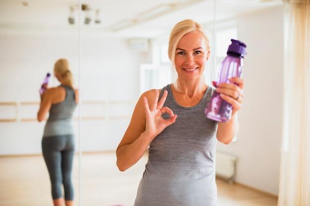 Donna senior adatta che tiene una bottiglia di acqua