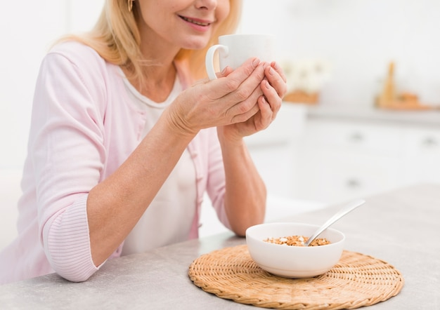 Donna senior adorabile del primo piano che mangia prima colazione