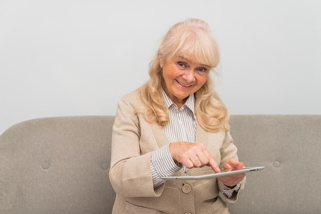Donna senior allegra che tocca lo schermo digitale della compressa con il dito