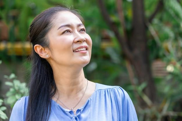 Donna senior asiatica che pensa e che si rilassa al parco.