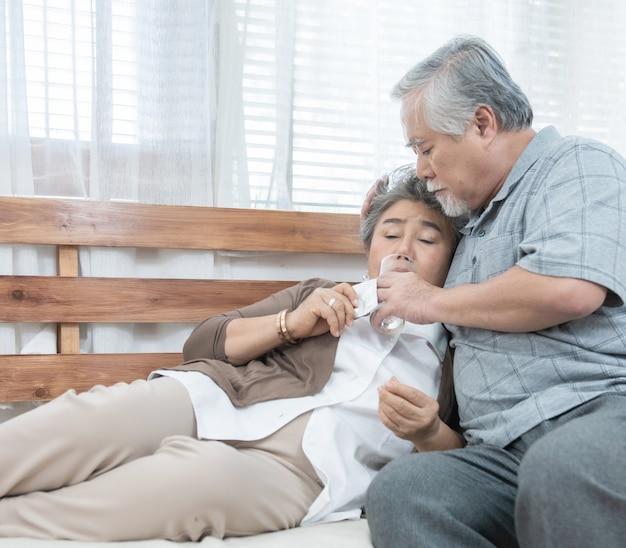 Donna senior asiatica che prende le medicine e l'acqua potabile mentre sedendosi sullo strato. l'uomo anziano si prende cura di sua moglie mentre la sua malattia alla casa concetto di sanità e medicina.