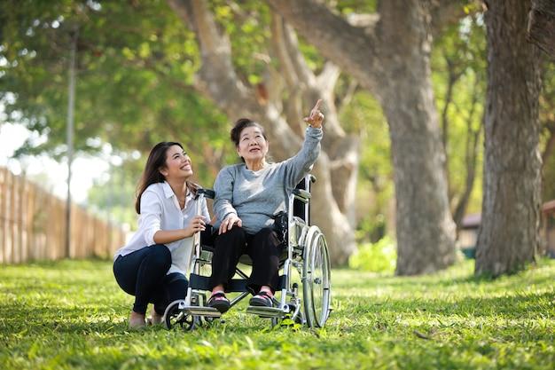 Donna senior asiatica che si siede sulla sedia a rotelle con il suo fronte felice di sorriso della sua famiglia del daugther sul parco verde