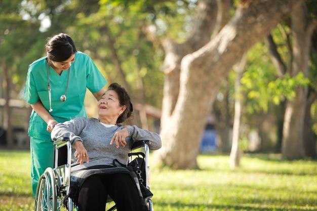 Donna senior asiatica che si siede sulla sedia a rotelle con la donna in uniforme di medico nell'ospedale del parco