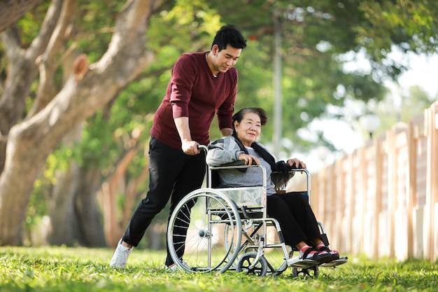 Donna senior asiatica che si siede sulla sedia a rotelle con suo fronte felice di sorriso del figlio sul parco verde