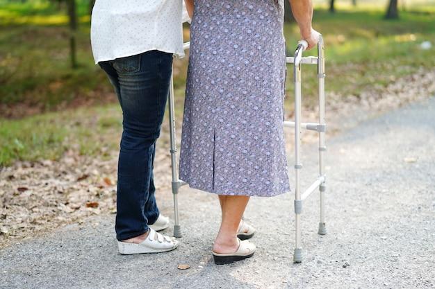 Donna senior asiatica che usando un camminatore al parco