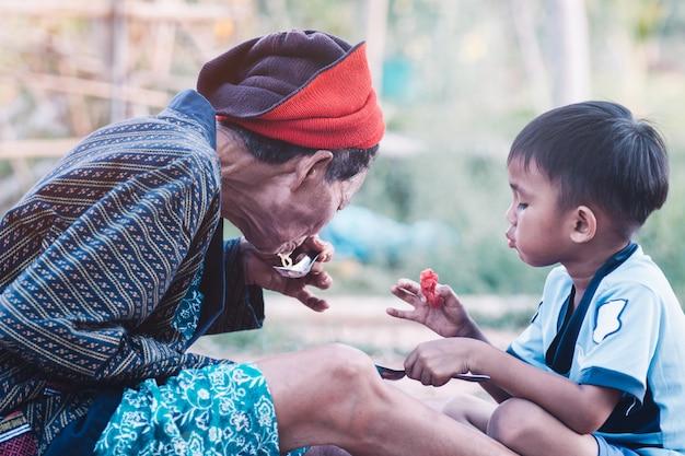 Donna senior asiatica e suo nipote che mangiano anguria con il sorriso e felici