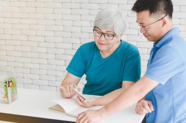 Donna senior asiatica felice che impara usare smartphone