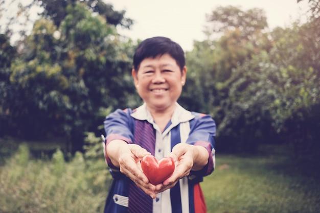 Donna senior asiatica sembrante naturale felice e in buona salute che tiene cuore rosso in un giardino