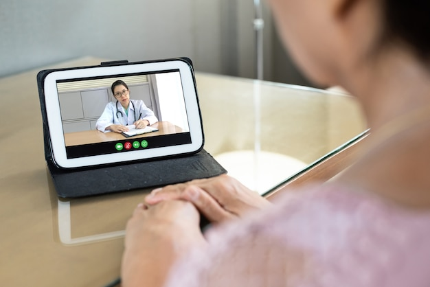 Donna senior asiatica sollecitata che parla e che consulta la dottoressa dei suoi sintomi da coronavirus via internet e tecnologia wireless.