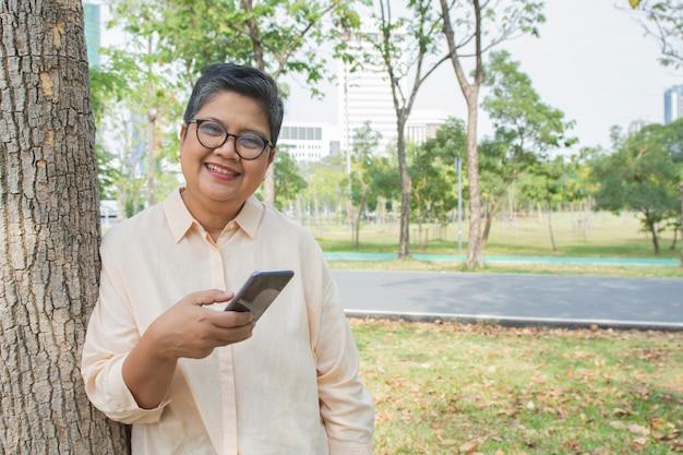 Donna senior attraente in vestito casuale e vetri di usura che stanno contro l'albero nella messaggistica del giardino con il suo cellulare mobile astuto.