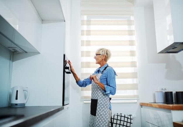 Donna senior bionda attraente in grembiule che sta nella cucina e che regola forno alla giusta temperatura