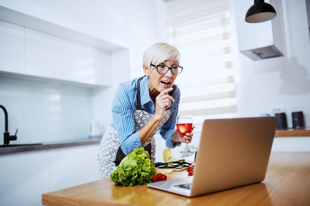 Donna senior bionda attraente sorridente in grembiule facendo uso del computer portatile per la ricetta e bevendo vino
