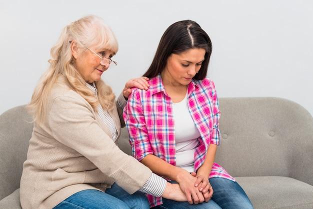 Donna senior bionda che dà conforto a sua figlia che si siede sul sofà