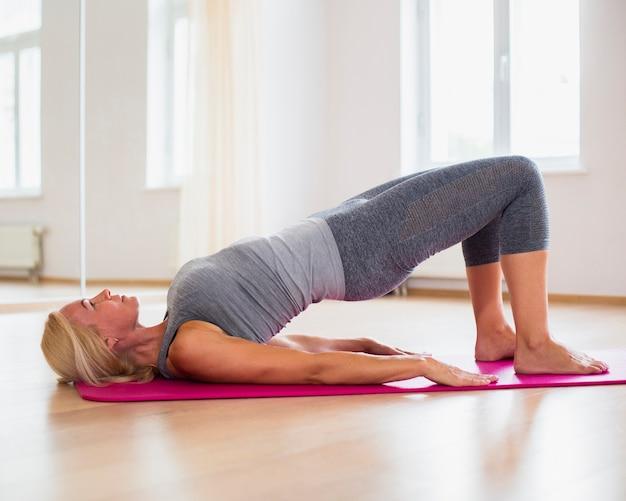 Donna senior bionda che esercita yoga