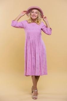 Donna senior bionda che posa in un vestito rosa