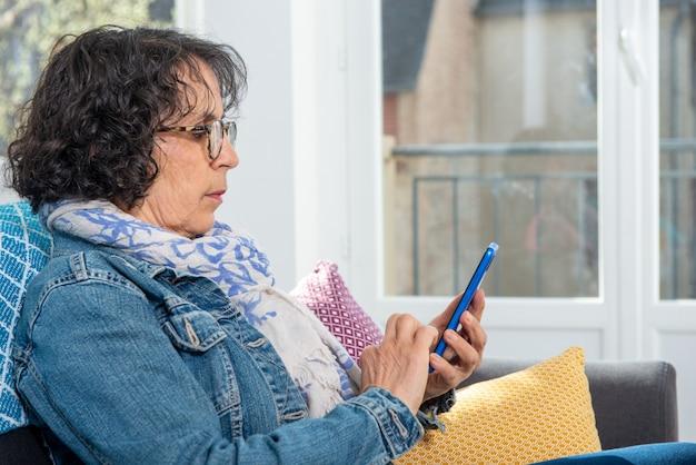 Donna senior castana allegra che per mezzo dello smartphone mentre sedendosi sul sofà