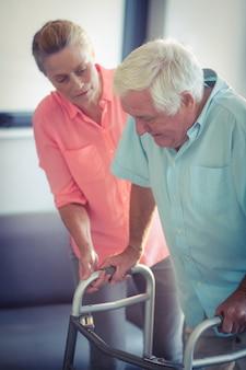 Donna senior che aiuta uomo senior a camminare con il camminatore