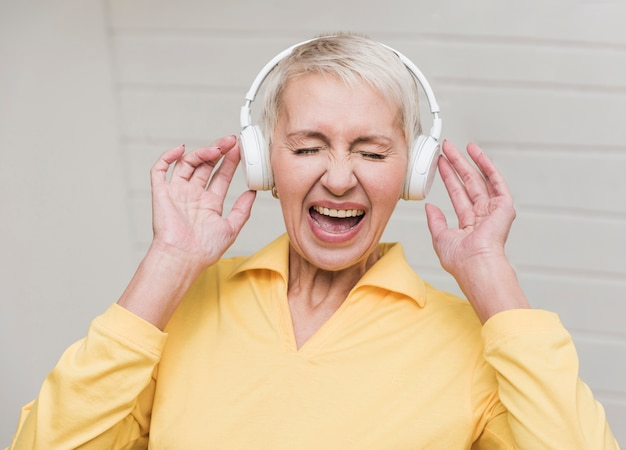 Donna senior che ascolta la musica rumorosa
