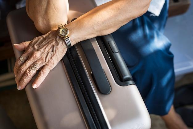 Donna senior che aspetta con i suoi bagagli in un hotel