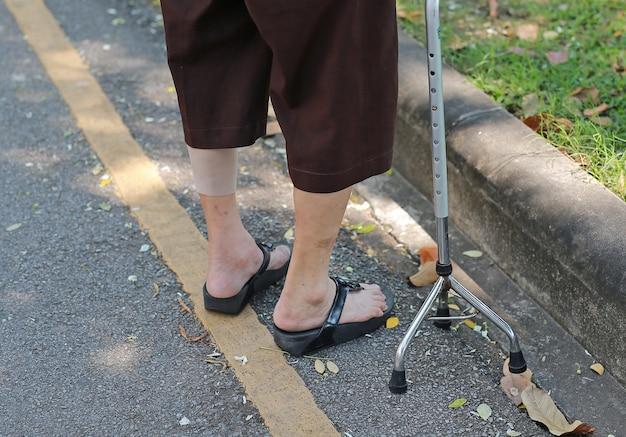 Donna senior che cammina con il bastone di alluminio nel parco