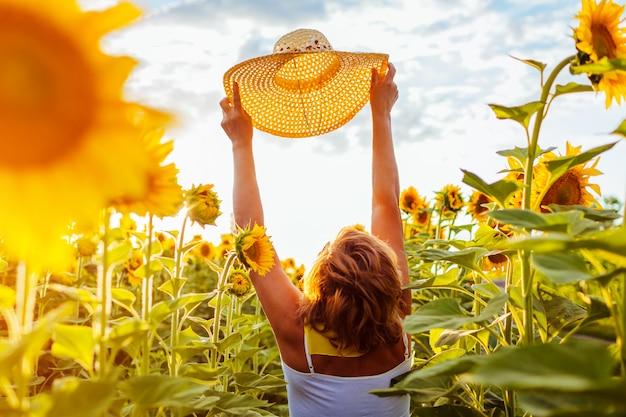 Donna senior che cammina in cappello di fioritura della tenuta del giacimento del girasole e vista piena d'ammirazione. vacanze estive