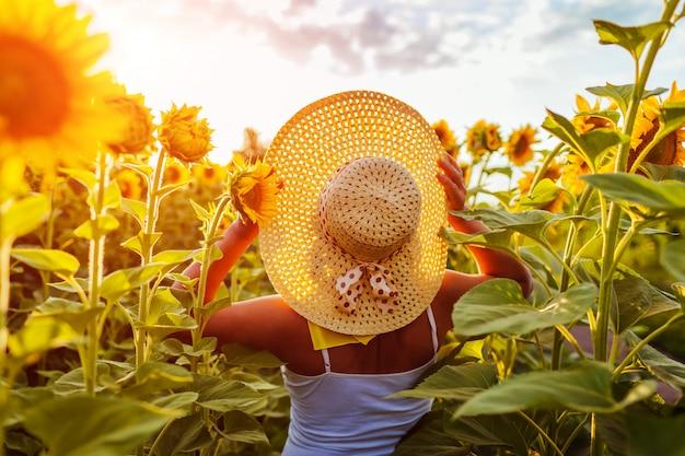 Donna senior che cammina in cappello di fioritura della tenuta del giacimento del girasole e vista piena d'ammirazione.