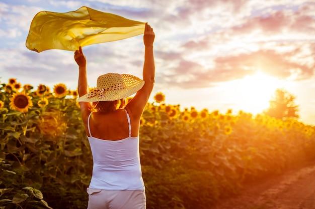 Donna senior che cammina nel giacimento di fioritura del girasole che solleva le mani con la sciarpa e divertiresi. vacanze estive
