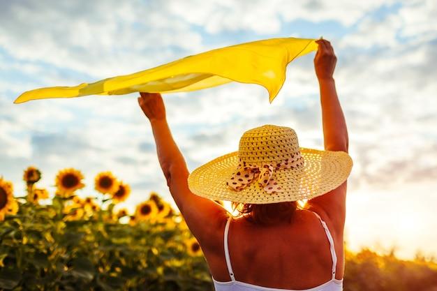 Donna senior che cammina nel giacimento di fioritura del girasole che solleva le mani con la sciarpa e divertiresi.