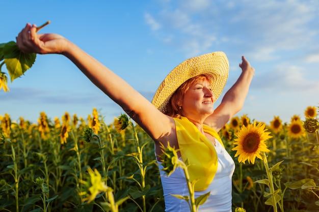 Donna senior che cammina nel giacimento di girasole di fioritura che si sente libero e che ammira vista.