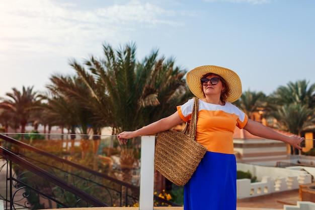 Donna senior che cammina sul territorio dell'hotel nell'egitto. vacanze estive tropicali. look alla moda e alla moda