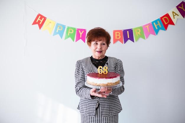 Donna senior che celebra il suo birthay a casa. tenendo la torta di compleanno su sfondo bianco