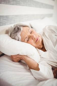 Donna senior che dorme sul letto in camera da letto